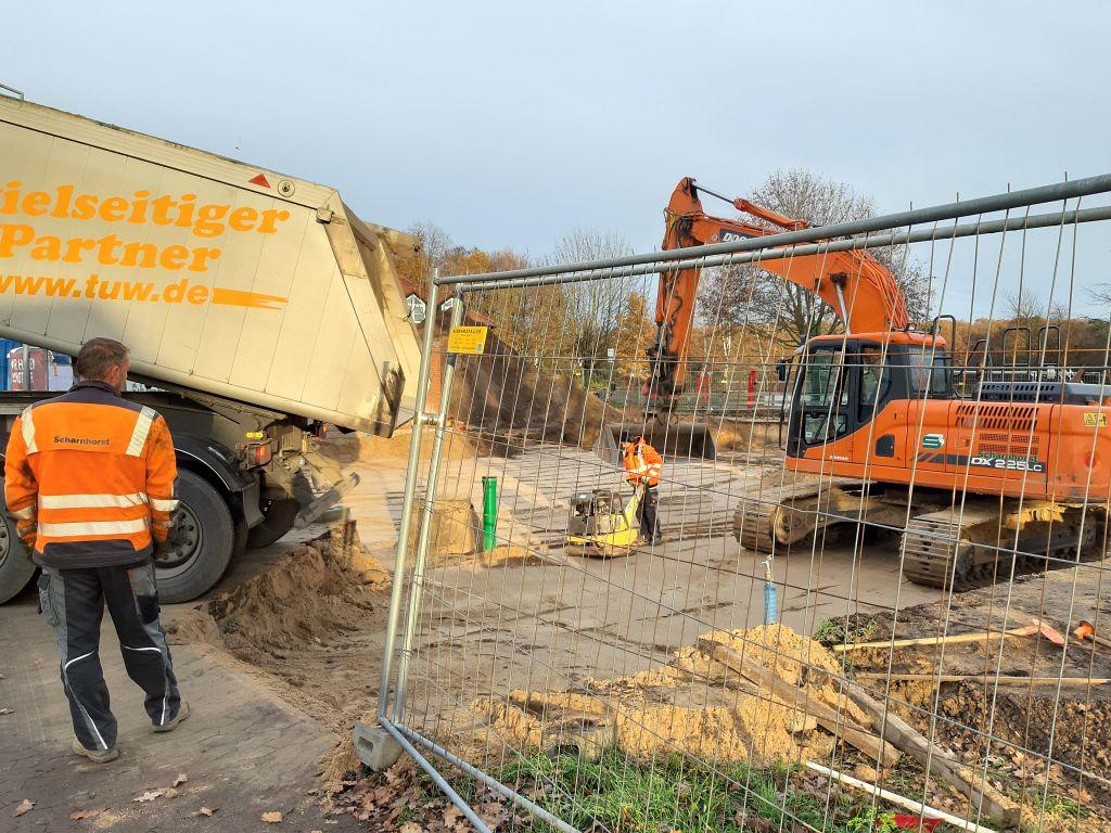 Auf dem Foto wird ein LKW gezeigt, der Rückwärts in die Baustelle einfährt und Sand abkippt.