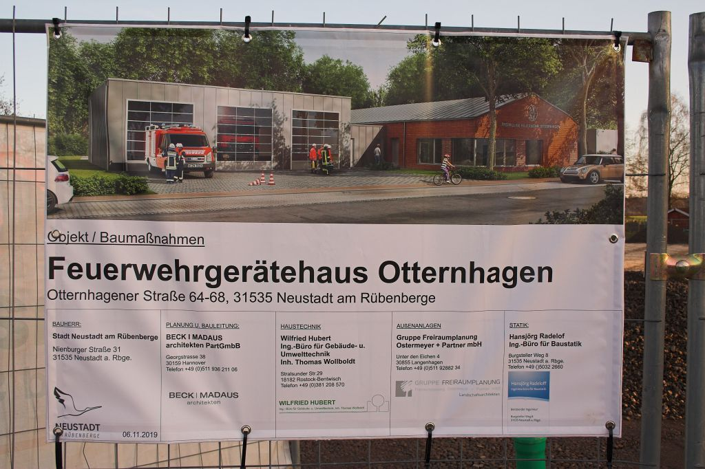 Das Foto zeigt ein Bauschild, das am Bauzaun angebracht ist. Es informiert über die Baumaßnahme Feuerwehrgerätehaus Otternhagen und zeigt eine Ansicht des künftigen Gebäudes.