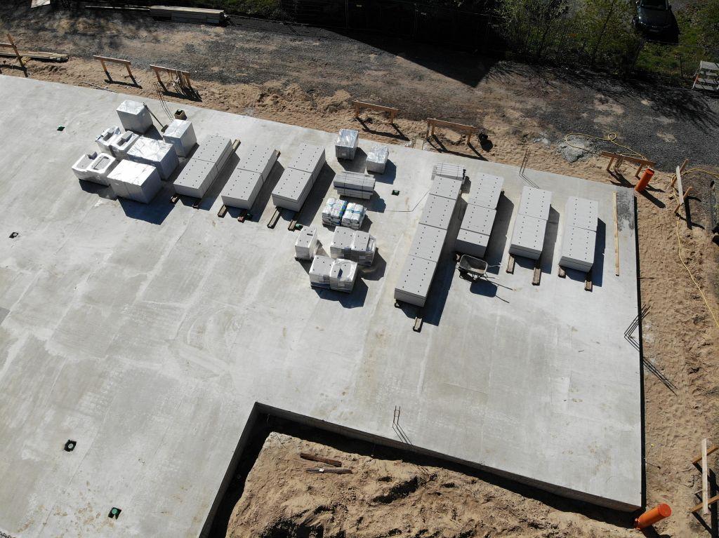 Die Aufnahme zeigt Bauteile für den weiteren Aufbau, die auf der fertigen Bodenplatte des Dienstgebäudes lagern.