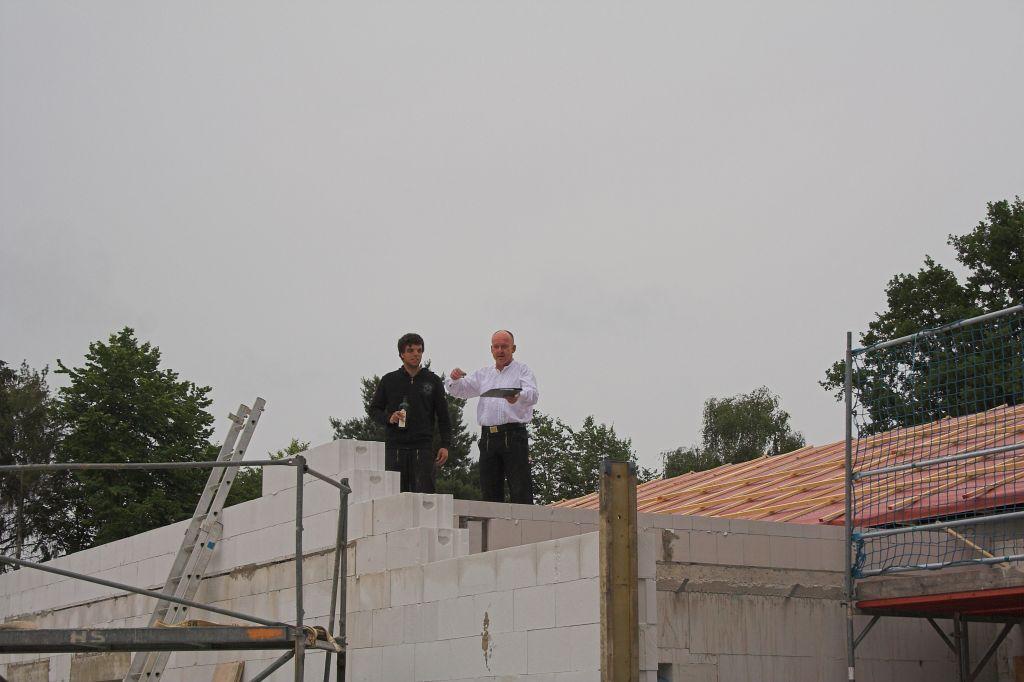 Auf dem Foto hält Dachdeckermeister und Geschäftsführer Mario Dammann den feierlichen Richtspruch. Links daneben: Dachdecker und Feuerwehrkamerad Tim Gödecke.