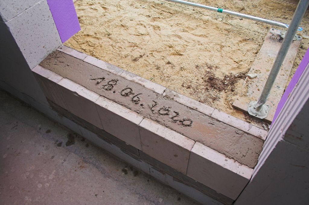 Das Foto zeigt die Betonfüllung, die mit einem Glattstrich und dem Datum der Grundsteinlegung versehen wurde.