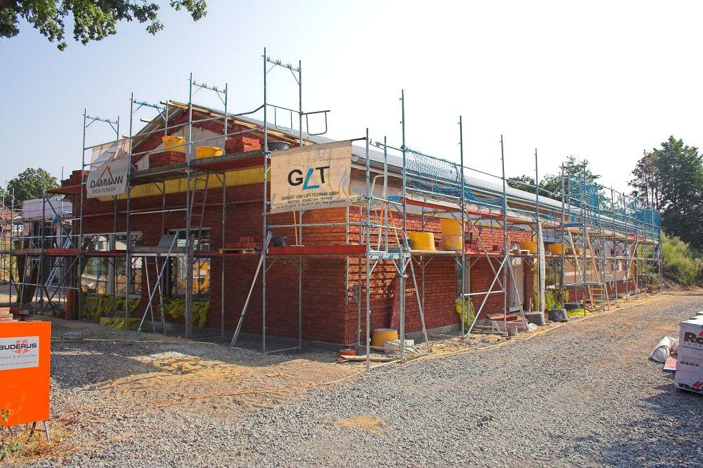 Das Foto zeigt eine Frontansicht des Dienstgebäudes: Auch in diesem Bereich sind die Arbeiten an der Klinkerfassade weit vorangeschritten.