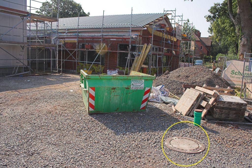 Das Bild zeigt den Kanaldeckel heute: Heute befindet sich der Kanaldeckel vor der neuen Fahrzeughalle. Die weißen Markierungslinien der ehemaligen Sperrfläche sind immer noch sichtbar. (Gelb markiert)