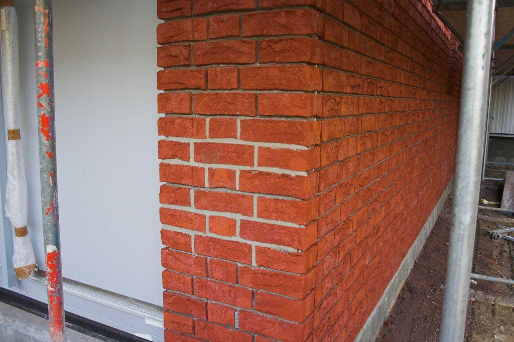 Die Abbildung zeigt, wie auf der Rückseite des Dienstgebäudes ein kleiner Bereich der Klinkerfassade verfugt wurde.