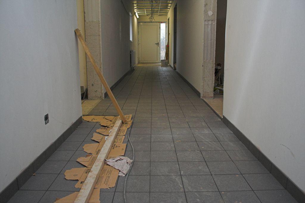 Die Abbildung zeigt die Verlegung von Bodenfliesen im Flur des Dienstgebäudes.