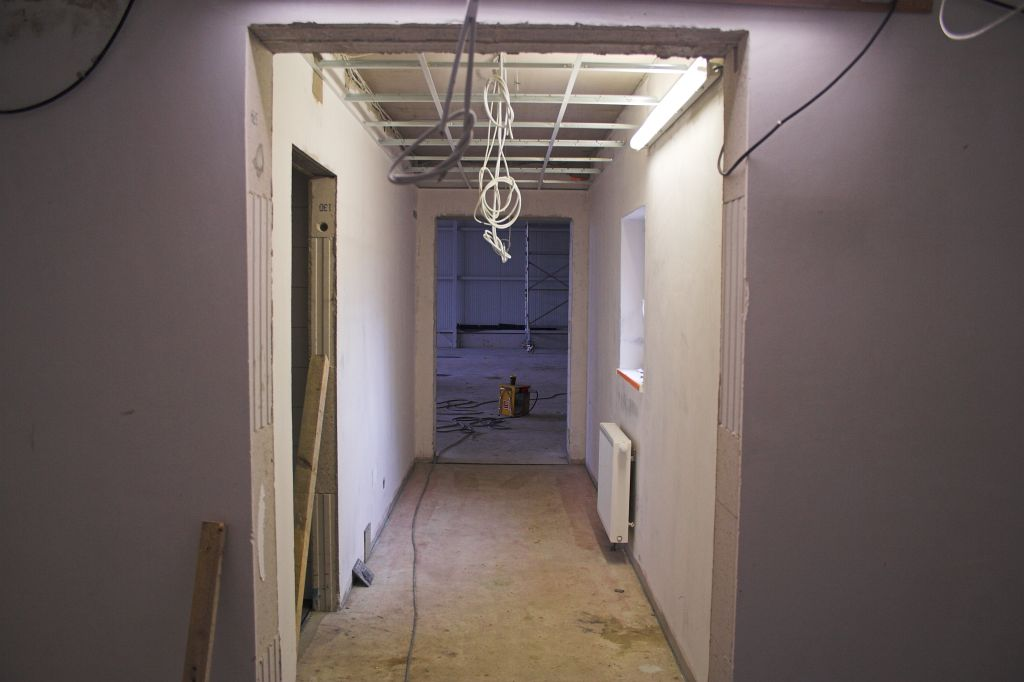 Dieses Foto zeigt den Blick vom Flur des Dienstgebäudes durch das Verbindungsbauwerk in die Fahrzeughalle.