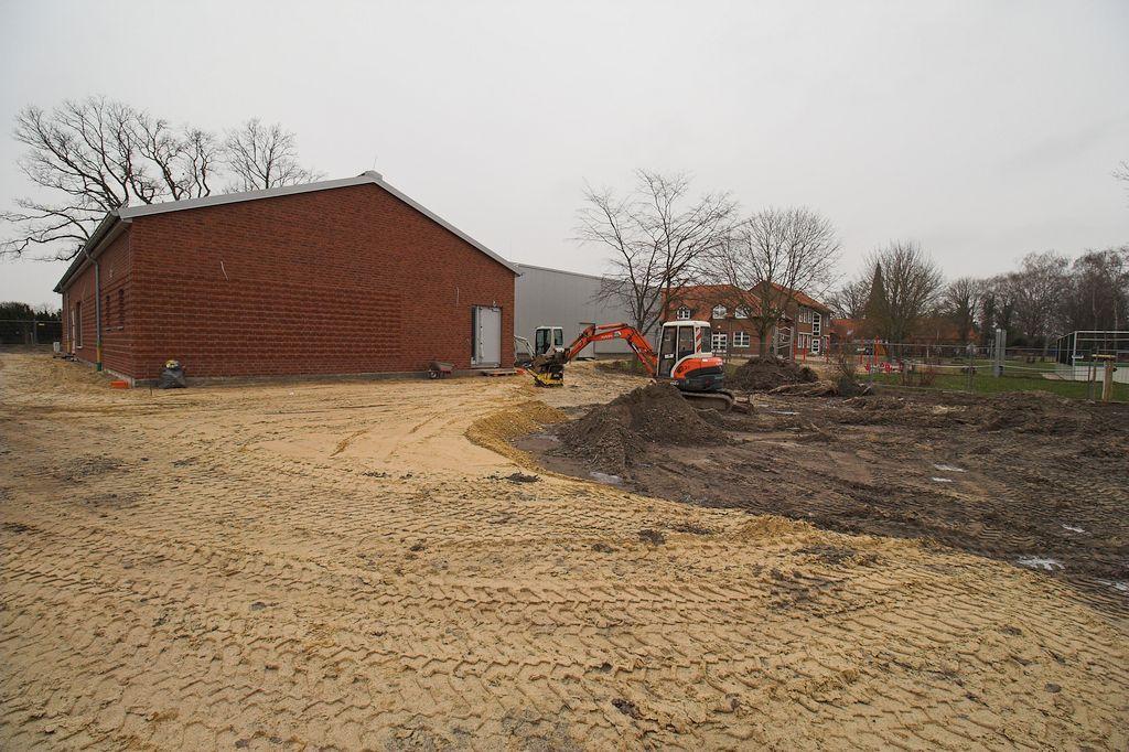 Das Foto zeigt, dass auf der Gebäuderückseite Erdarbeiten stattfinden. Hier entsteht ein Parkplatz.