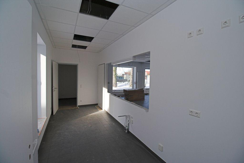 Das Foto zeigt den Küchenbereich mit Durchreiche zum Schulungsraum und Zugang zum Lagerraum.