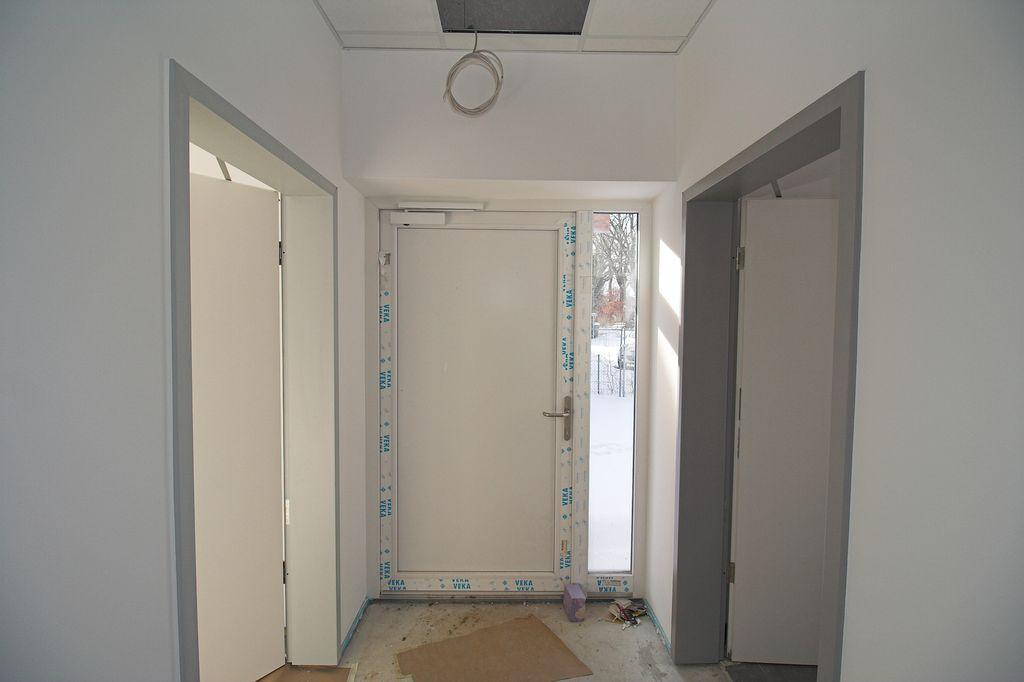 Zugangsbereich mit Haupteingang (in der Bildmitte), Durchgang zum Büroraum (linke Tür) und Zugang zum Küchenbereich (rechte Tür).