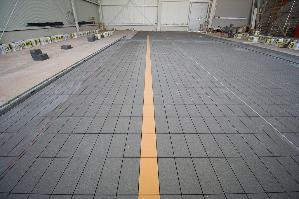 Das Foto zeigt ein Detail: Bodenfliesen in der Fahrzeughalle - mit eingearbeiteter Orientierungslinie.