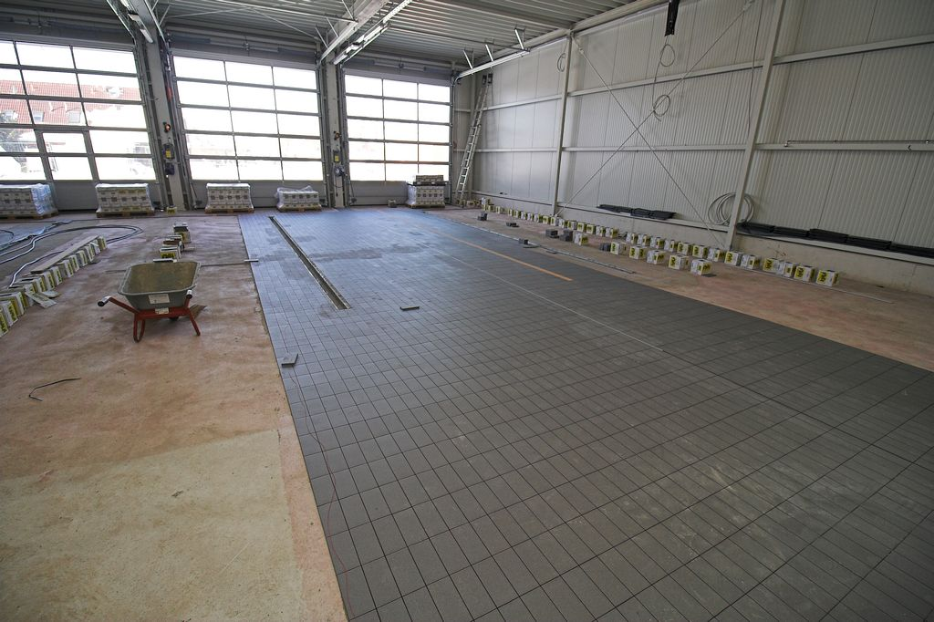Auf dem Foto wird gezeigt, dass in der Fahrzeughalle zurzeit Bodenfliesen verlegt werden.
