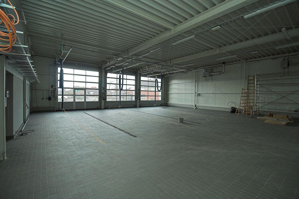 Die Fliesenarbeiten in der Fahrzeughalle sind abgeschlossen. Der Hallenboden ist vollständig gefliest.