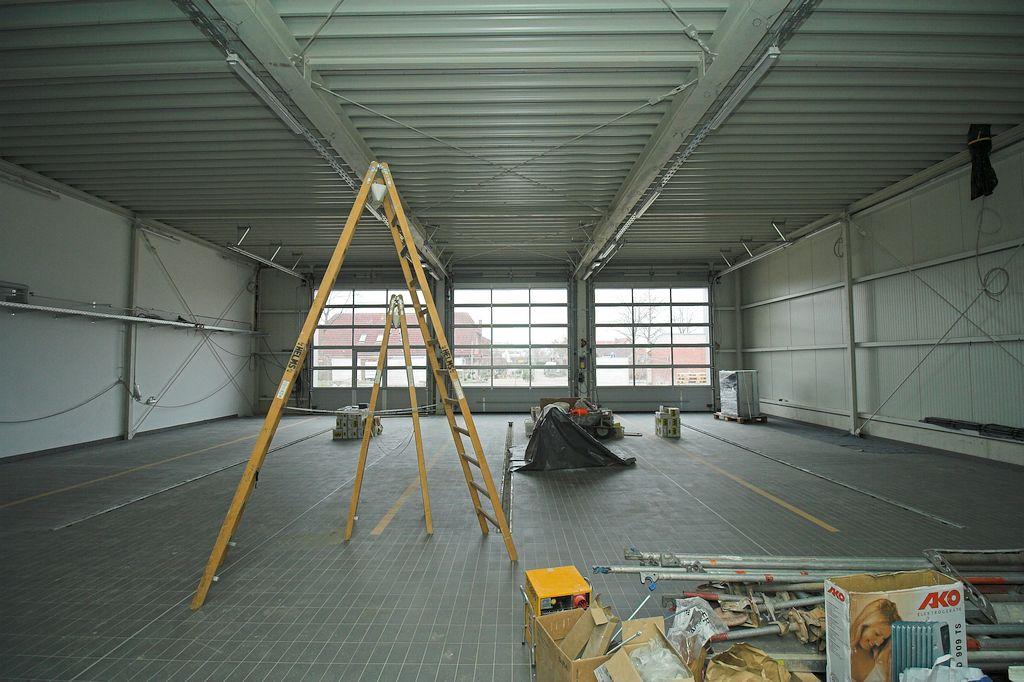 Die Verlegung der Bodenfliesen in der Fahrzeughalle ist nahezu abgeschlossen.
