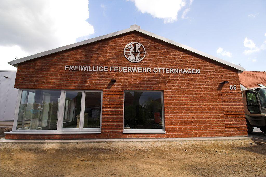 Das Foto zeigt, wie das Feuerwehrsymbol sowie die Beschriftung an der Giebelseite des Dienstgebäudes deutlich sichtbar auf das neue Feuerwehrgerätehaus Otternhagen hinweisen.