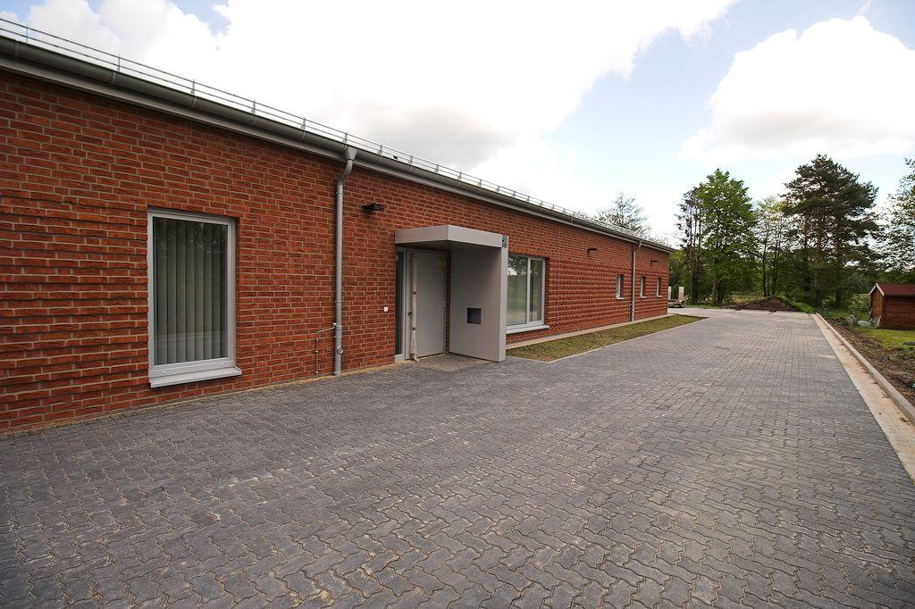 Das Foto zeigt die fertiggestellte Zufahrt zum Parkplatz auf der Gebäuderückseite und den Haupteingang des Dienstgebäudes.