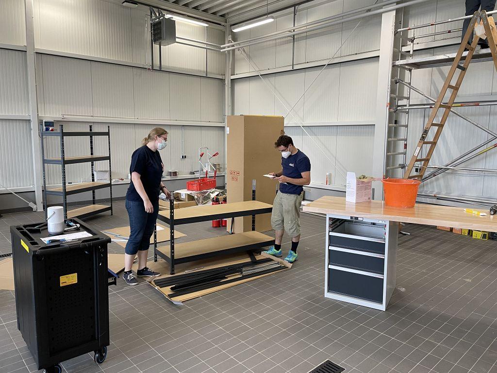Das Foto zeigt den Aufbau von Regalen in der Fahrzeughalle des neuen Feuerwehrgerätehauses in Otternhagen.