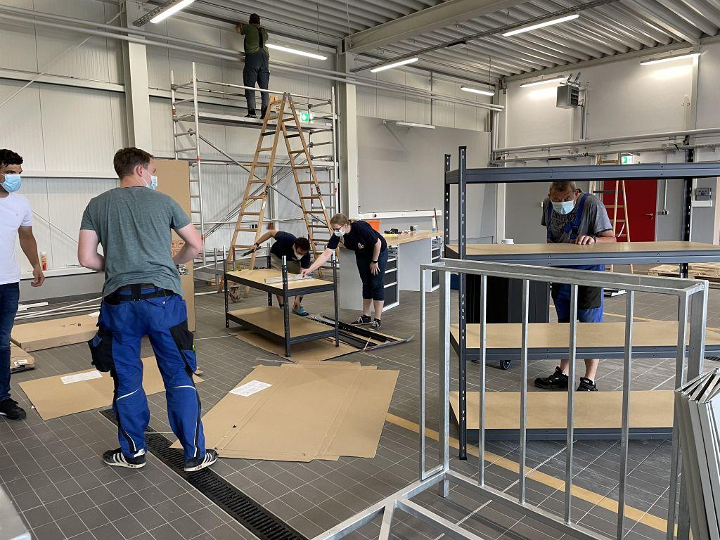 Reges Treiben: In der Fahrzeughalle sind Feuerwehrkameradinnen und -kameraden damit beschäftigt, die Regale, Schränke und weitere Ausstattungen auf- und einzubauen.