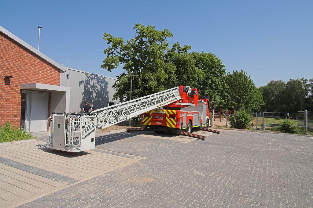 Das Foto zeigt, wie die DLK32/12 auf dem Parkplatz hinter dem Feuerwehrgerätehaus aufgestellt wird.