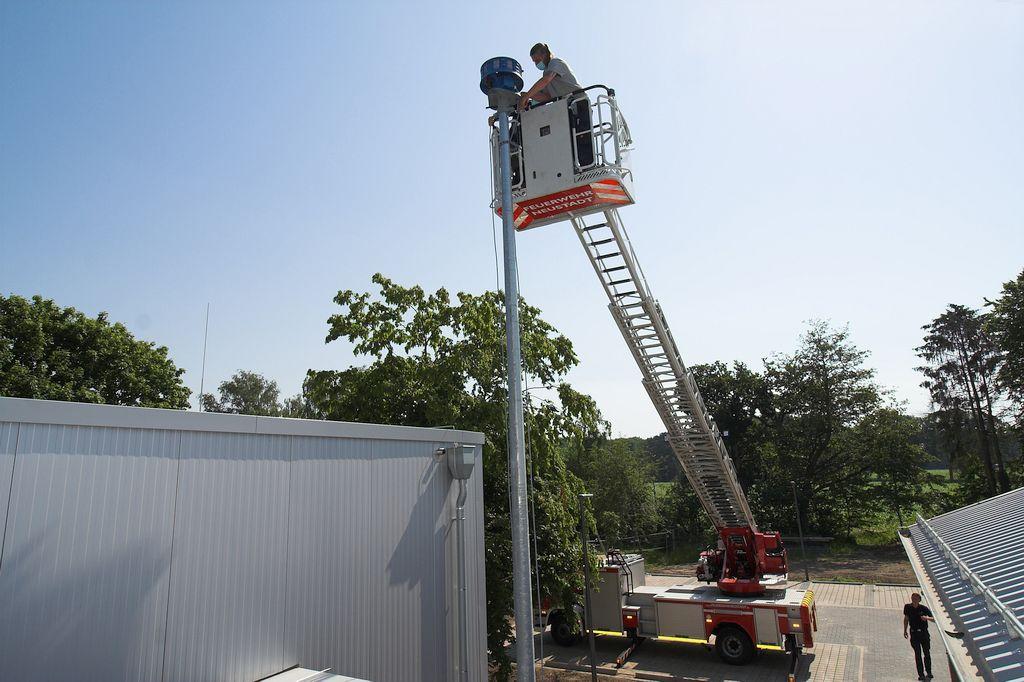 Die Aufnahme zeigt, wie die Sirene mit der Montageplatte verschraubt wird und das Anschlusskabel durch den Masten zum Anschlusskasten geführt wird.
